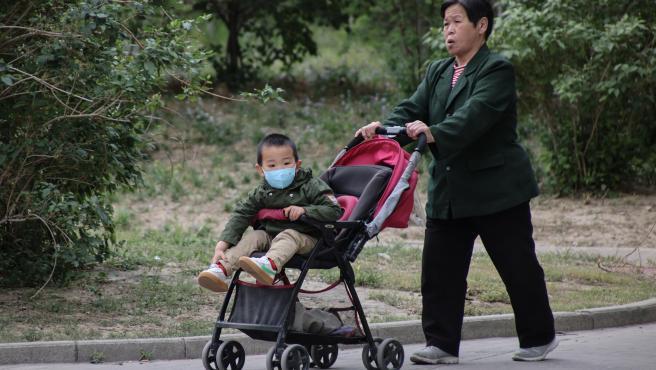 Una mujer pasea a un niño en un cochecito en Pekín, China.