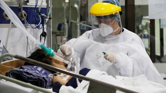 Una sanitaria atiende a un paciente de covid-19.