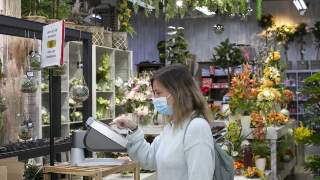 Una mujer extrae un ticket para ser atendida en uno de los comercios que participan en la prueba piloto, la floristería Flores Navarro.
