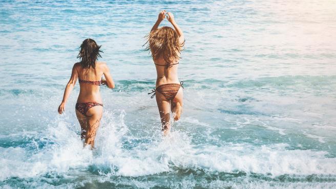 Dos jóvenes se bañan en una playa.