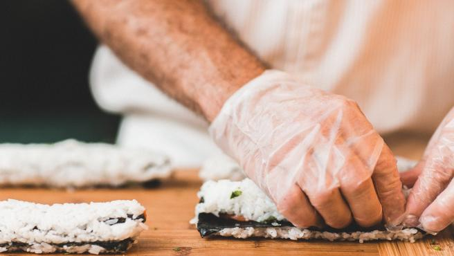Persona preparando sushi.