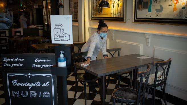 Una camarera limpia una mesa de un restaurante de Barcelona, en una imagen de archivo.