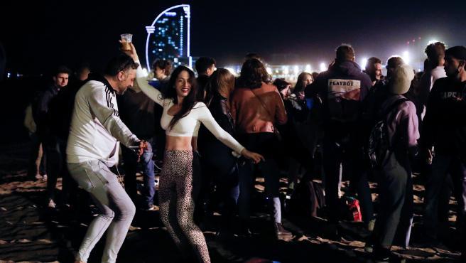 Dos jóvenes rodeados por centenares de personas bailan en la playa de la Barceloneta.
