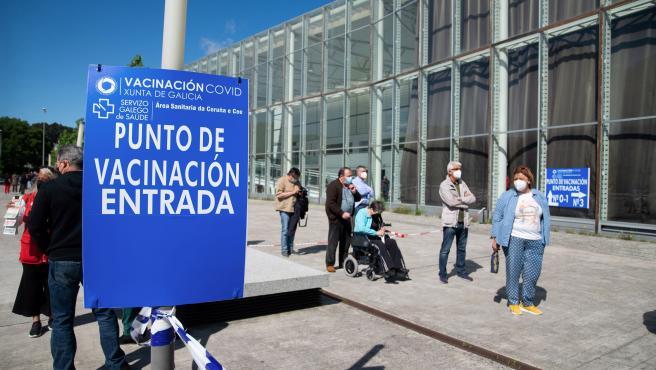 Varias personas hacen cola en un punto de vacunación contra la Covid-19 en A Coruña.