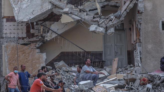 La defensa civil palestina busca personas entre los escombros de una casa destruida.