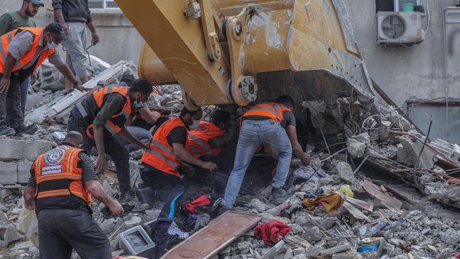 Operarios palestinos tratan de recuperar víctimas entre los escombros.