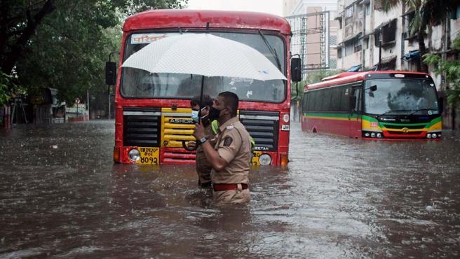 Un policía ayuda a un conductor a cruzar una calle inundada por el ciclón Tauktae en Bombay.