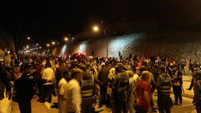 Jóvenes marroquíes esperan el momento de cruzar la frontera en la localidad marroquí de Castillejos.