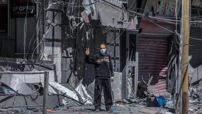 Un palestino hace el signo de la victoria frente a su casa, destruida por un bombardeo israelí, en Gaza.
