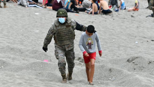 Un militar del ejército español acompaña a un niño en una jornada marcada por las devoluciones en caliente que están efectuando a los migrantes que han entrado en Ceuta procedente de Marruecos.