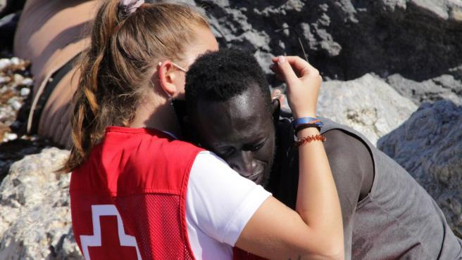 """Las imágenes de los miles de ciudadanos africanos llegados a las costas de Ceuta en una crisis migratoria sin precedentes en España han dado la vuelta al mundo y no han dejado indiferente a nadie. Detrás de una de estas fotografías que han encogido el corazón a lectores y espectadores se encuentra Luna, la joven trabajadora de la Cruz Roja que trataba de consolar este martes a uno de los recién llegados a la ciudad autónoma.  Tiene 20 años, es de Móstoles y se encuentra en Ceuta -ciudad natal de su madre, Inma- para hacer las prácticas del Grado Superior de Integración Social, según recoge la cadena Ser. Allí intentó aliviar el sufrimiento de quienes acababan de llegar a suelo español, entre ellos, un joven migrante que la abrazaba desconsolado mientras ella le ofrecía agua y respaldo.  """"Se me cae el puto alma al suelo"""", se desahogaba Luna en su cuenta de Twitter (Hija del camino) para resumir todo lo que había sentido durante el día, de acuerdo con El Mundo. Y añadía: """"No creo en ningún Dios, pero estoy segura de que si viviera las situaciones que ha vivido esta gente lo haría""""."""