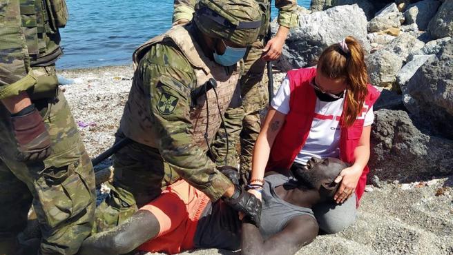 Luna y miembros del Ejército de Tierra ayudan al inmigrante tras cruzar a Ceuta.