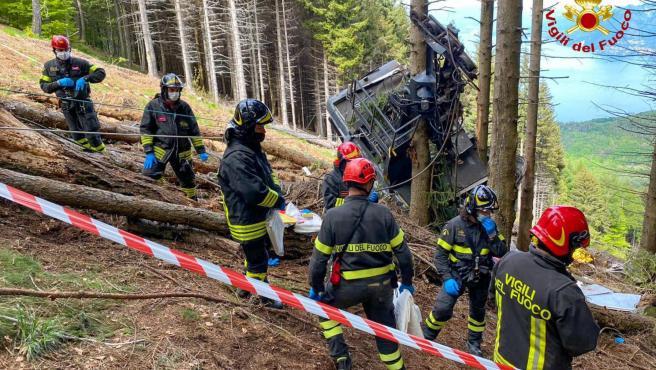 Bomberos junto a los restos de la cabina del teleférico Stresa-Mottarone.