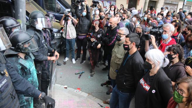 Los diputados de la CUP Dolors Sabater, Carles Riera, Xavier Pellicer y Eulàlia Reguant delante de la línea policial, durante el desahucio del 'bloc Llavors' de Barcelona.