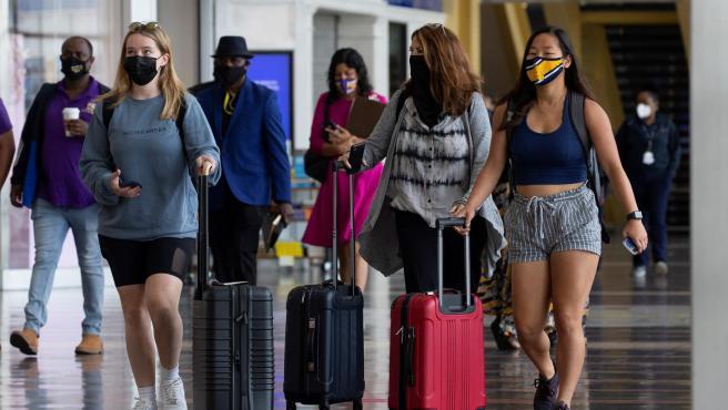 Viajeros con mascarillas por el coronavirus, en el aeropuerto Ronald Reagan de Washington, en Arlington, Virginia (EE UU).