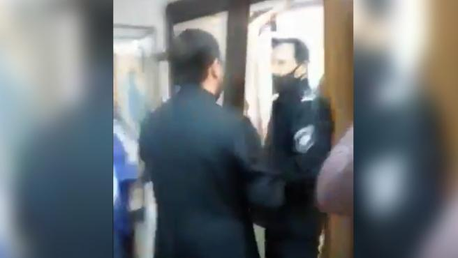 El sacerdote tratando de expulsar a la policía con una enorme cruz.