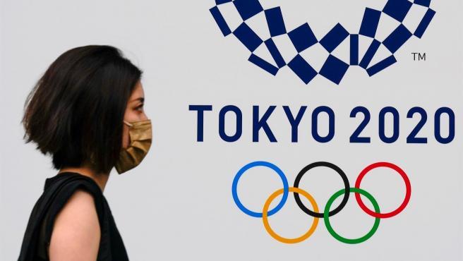 Una mujer con una máscara de coronavirus pasa junto a un cartel de los Juegos Olímpicos de Tokio en Tokio, Japón.