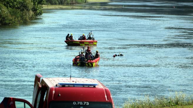 Un vehículo de emergencia aparcado en la playa de Miravet con dos embarcaciones buscando el río Ebro en Miravet, Tarragona.