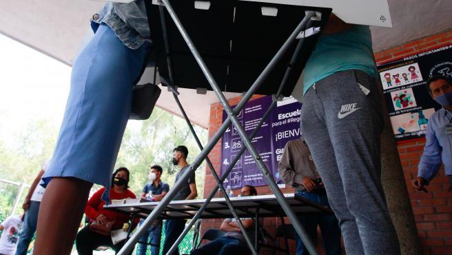 Dos personas, en una cabina de votación en México.