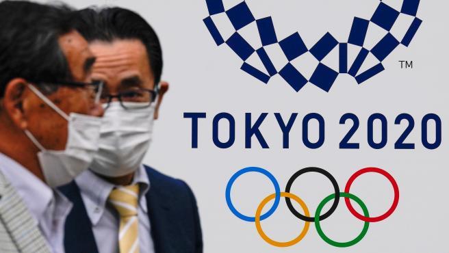 Dos hombres, ante un cartel de los Juegos Olímpicos de Tokio 2020