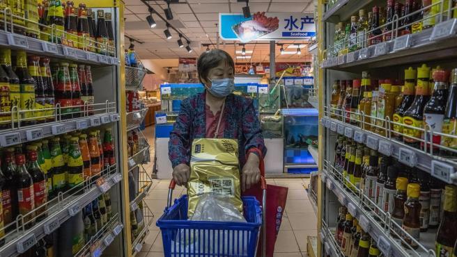 Una mujer con mascarilla por la pandemia de covid-19, en un supermercado de Pekín, China.