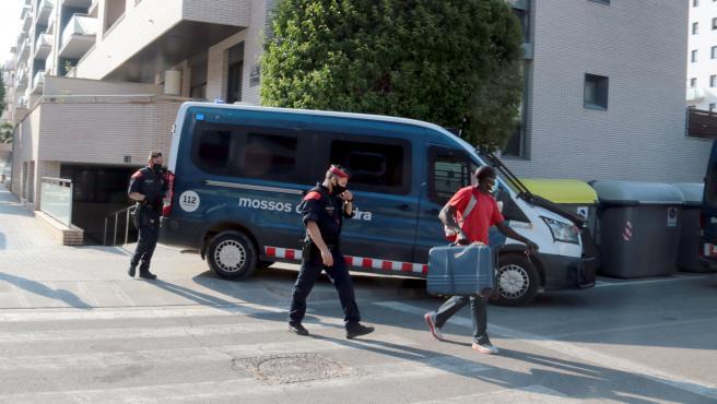 Una de las personas desalojadas de un edificio ocupado de Lleida, acompañada de Mossos.