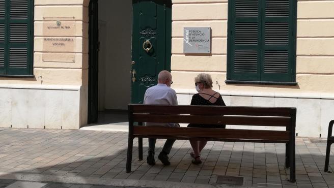 Imagen de archivo de dos personas mayores sentadas en un banco.