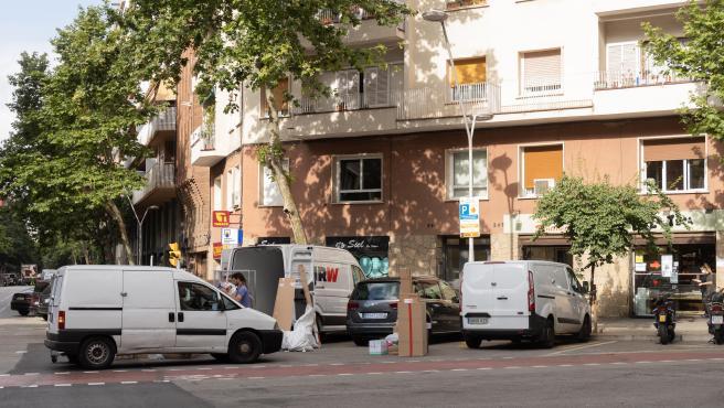Un repartidor de paquetería estacionado en un chaflán del centro de Barcelona, rodeado de otras furgonetas en doble fila.
