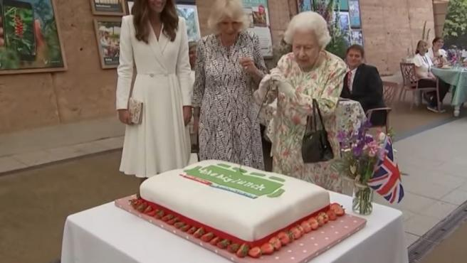 La reina de Inglaterra, partiendo una tarta conmemorativa junto a su nuera y la mujer de su nieto.