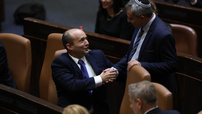 Neftali Bennett, a la izquierda, felicitado por un político en el parlamento de Israel.
