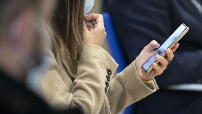 Una chica emplea un teléfono móvil.