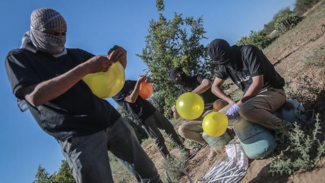 Varios palestinos llenas unos globos de gas refrigerante, muy inflamable, antes de ser lanzados hacia territorio israelí.