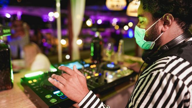 Young african DJ man mixing music at club outdoor while wearing safety face mask for coronavirus outbreak