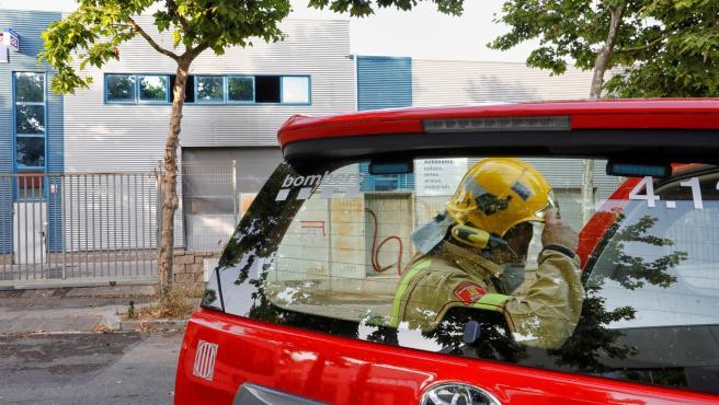 Bomberos trabajando en el incendio de un taller mecánico en el que murió un bombero, en Vilanova i la Geltrú (Barcelona).