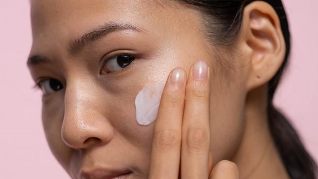 Una mujer se aplica crema facial en el rostro.