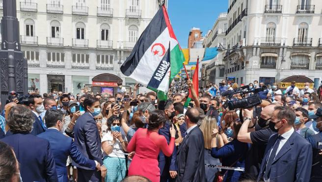 Díaz Ayuso, en el centro de la imagen, ha sido aclamada por decenas de personas que se concentraban en Sol, donde había una manifestación a favor de la autodeterminación del Sáhara Occidental.