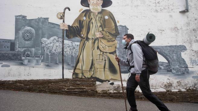 Portomarin, Lugo. Gabriel Liaño, peregrino madrileño que realiza por segunda vez el Camino, pasa frente a un mural que representa a Zapatones, mítico e icónico peregrino que recibía hasta su fallecimiento a los pere