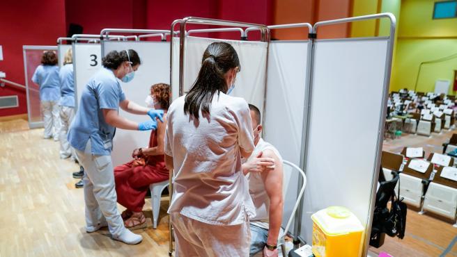 Dos personas reciben la primera dosis de la vacuna de Pfizer-BioNTech contra la Covid-19 en Madrid.