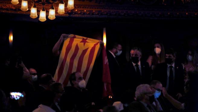 Una persona muestra una bandera independentista durante la conferencia de Pedro Sánchez