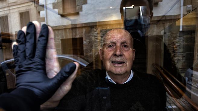 Visita a mi abuelo Miguel, de 90 años, durante el confinamiento que saluda a través del cristal del portal. El alto índice de personas mayores afectadas por la Covid-19 les obligó a un estricto aislamiento con la esp