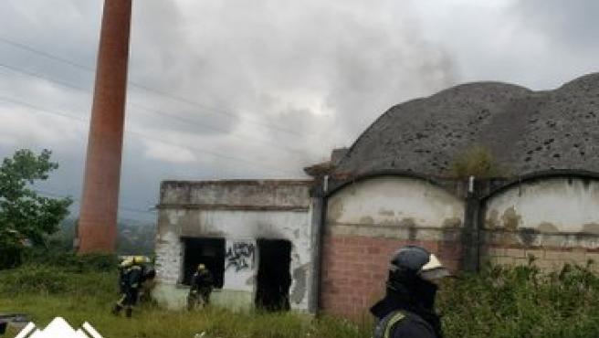 Los bomberos apagan el fuego de unos colchones y una moto en el interior de una nave abandonada de Siero
