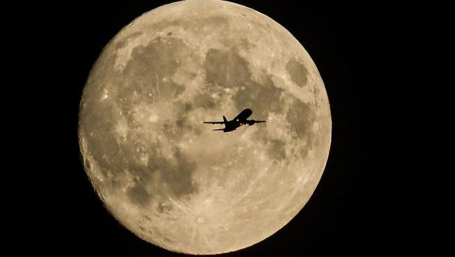 Un avión despega del aeropuerto de Moscú (Rusia), con la enorme superluna de fresa al fondo.