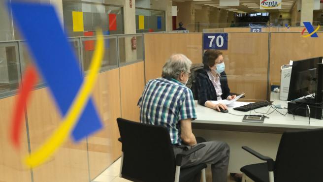 Una empleada atiende a una persona de manera presencial desde una oficina de la Agencia Tributaria.