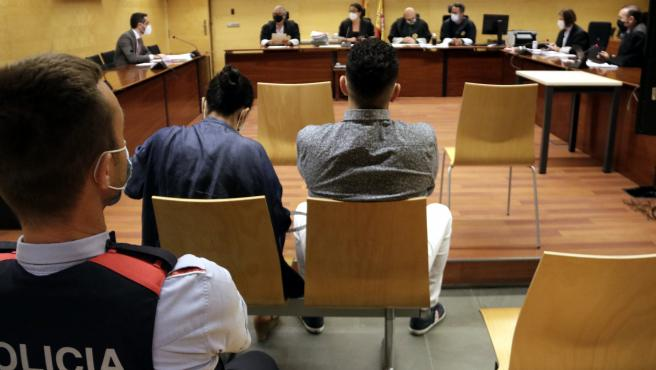 De espaldas y custodiado por los Mossos d'Esquadra, el acusado de violar a una chica y retenerla durante horas en su piso de Blanes (Girona), durante el juicio este martes 29 de junio de 2019.