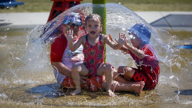 Unos niños se refrescan para aliviar la intensa ola de calor que vive Canadá estos días.