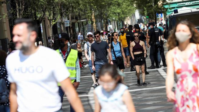 Varias personas pasean con y sin mascarilla, en el centro de Madrid.