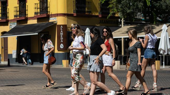 Un grupo de jóvenes sin mascarilla pasean por Sevilla.