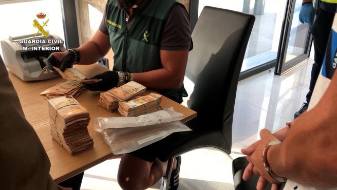 Un agente de la Guardia Civil cuenta el dinero incautado en una operación de narcotráfico en una imagen de archivo.