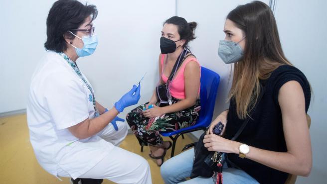 Una profesional sanitaria da unas explicaciones a unas jóvenes, en el centro de vacunación masiva de Cornellà (Barcelona).