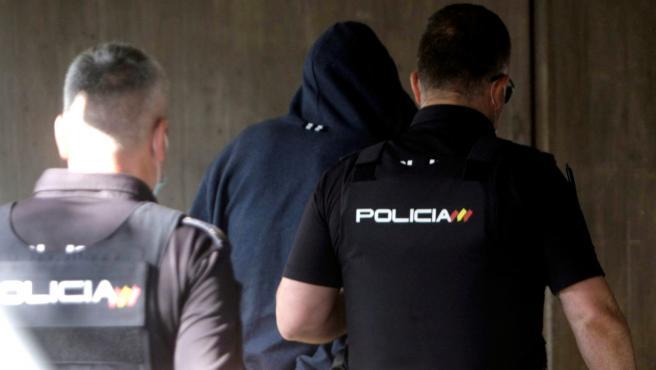 Agentes de la Policía Nacional conducen a uno de los cuatro detenidos